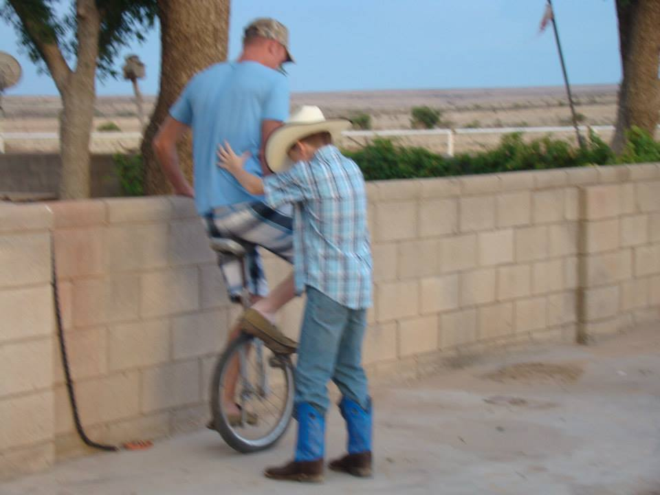 Jason trying to ride the unicycle with Brocks assistance